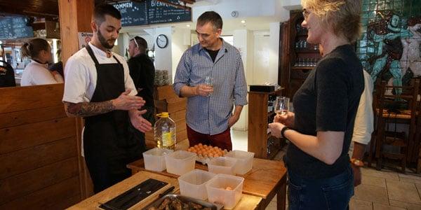Gourmetkokke der underviser gæster i at åbne østers.